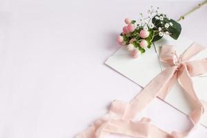 Umschlag auf weiß-rosa Hintergrund mit pfirsichfarbenem Seidenband foto