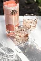 Roséwein in Gläsern und Flaschen. foto