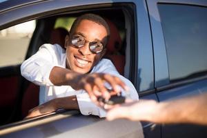 glücklicher Afroamerikaner in einem Auto mit Schlüssel, im Sommer foto