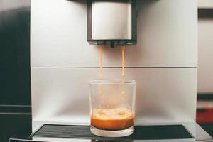 Nahaufnahme einer Kaffeemaschine, die einen Espresso-Kaffee zubereitet? foto