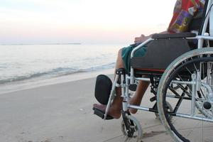 Alter Mann im Rollstuhl schaut vom Strand auf das Meer foto