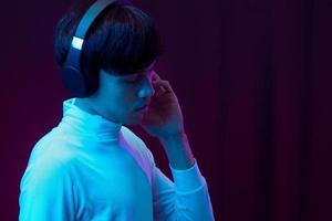 junger asiatischer mann, der musik mit kopfhörer im neonlicht hört foto