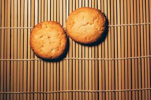 zwei runde knusprige Kekse, auf strukturiertem Bambus, schlichtes Design foto