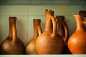weich fokussierte Weinkrüge in Terrakottafarbe auf dem Gestell foto
