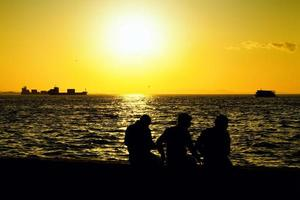 Menschensilhouette und das Meer im Sonnenuntergang foto