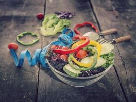 frischer Salat, Maßband auf Holztisch. gemischtes Gemüse, Tomaten foto