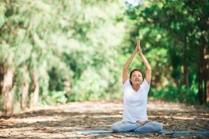 junge asiatische frau, die morgens yoga im park macht. foto