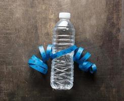 Plastikflasche Wasser mit Maßband über dem hölzernen Hintergrund foto