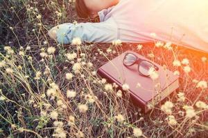 junge Frau, die nach dem Lesen des Buches auf dem Löwenzahnfeld ein Nickerchen macht. foto