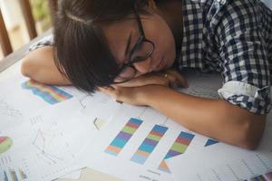 Müde Geschäftsfrau schläft auf einem Laptop, während sie an ihrem Arbeitsplatz arbeitet foto