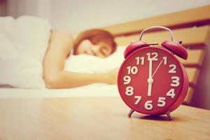 Frau schläft morgens mit rotem Wecker auf dem Bett. foto