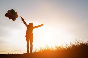 Silhouette der jungen Frau, die bunte Luftballons mit Sonnenuntergang hält foto