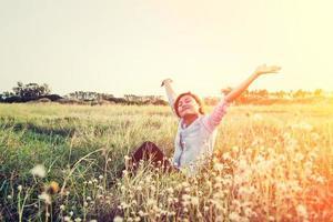 Schöne junge Hipster-Frau, die auf den Wiesen sitzt, dehnen sich so frisch aus foto