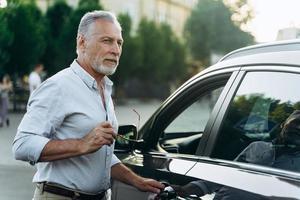 älterer Mann steht in der Nähe seines Geländewagens und hält eine Sonnenbrille. foto