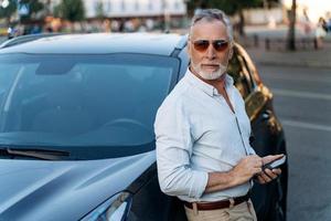 älterer Mann, der in der Nähe seines SUV-Autos steht und Smartphone hält. foto
