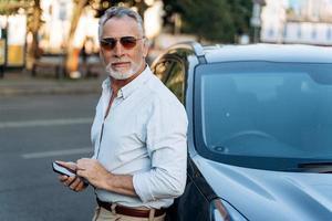 Mann mittleren Alters, der in der Nähe seines Geländewagens steht foto