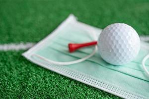 Golfball mit T-Stück auf der Gesichtsmaske zum Schutz des Covid-19-Coronavirus foto