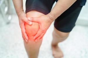 asiatische Dame schmerzt ihr Knie. foto