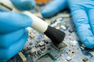 Techniker verwenden Bürste, um Staub im Platinencomputer zu reinigen foto