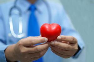 Arzt hält rotes Herz im Krankenhaus. foto