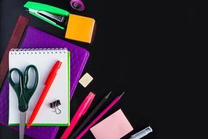 Satz Briefpapier auf schwarzem Hintergrund. zurück zum Schulkonzept foto