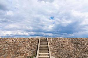 die Treppe zum Damm ist im Hintergrund mit Steinen gefüllt foto