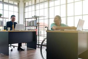 asiatische behinderte Frau im Gespräch mit Kollegen im Büro foto