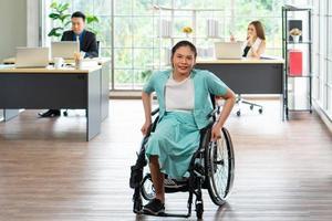 asiatische behinderte frau, die im rollstuhl sitzt und im büro arbeitet foto