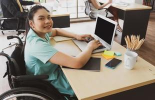 behinderte Frau sitzt im Rollstuhl und arbeitet im Büro foto