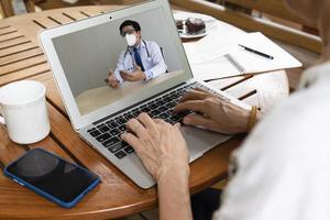 Seniorin konsultiert asiatischen Arzt per Videoanruf foto