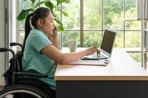 Junge behinderte Frau, die Computer und Smartphone verwendet, um im Büro zu arbeiten foto