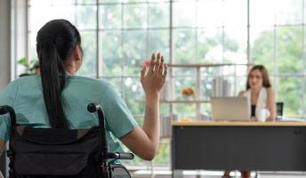 junge behinderte Frau grüßt Freund im Büro foto