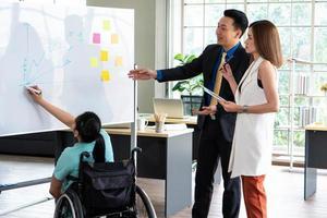 asiatische behinderte frau präsentiert projekt im konferenzraum foto