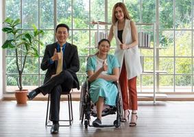 Junge behinderte Frau sitzt mit ihren Kollegen im Büro im Rollstuhl foto