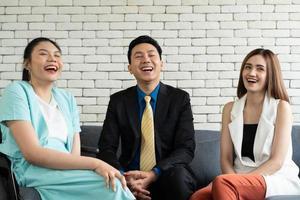 asiatische behinderte frau, die mit kollegen im büro lacht foto