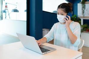 Frau trägt Maske und verwendet Computer für Videoanrufe im Co-Arbeitsraum. foto