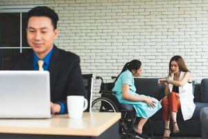 Geschäftsmann, der im Büro arbeitet, während Kollege auf der Couch sitzt foto
