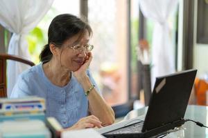 Senior asiatische Frau, die Computer verwendet, um E-Mails an Freunde zu Hause zu senden foto