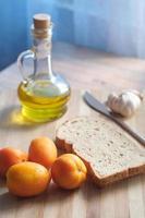 Nahaufnahme von Knoblauch, Tomaten und Olivenöl auf dem Tisch foto