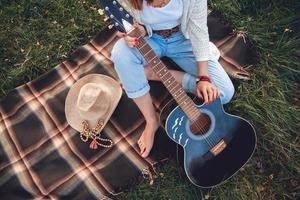 schöne Frau mit Gitarre ruht auf grünem Rasen foto