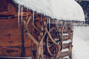 Eiszapfen hängen vom Dach eines Holzhauses foto