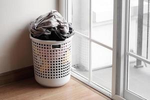 Plastikkorb mit schmutziger Wäsche auf dem Boden foto