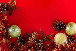 festliche Komposition aus Zapfen und Weihnachtskugeln auf rotem Grund foto