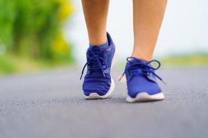 Frauenfüße, die auf der Straße laufen, gesundes Fitnessfrauentraining foto