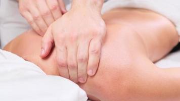 Mann Therapeut, der Massage an Patientin tut, die auf der Couch im Spa-Schrank liegt. weiblicher Kunde, der in der Schönheitsklinik eine Massage zur Verjüngung erhält. Massage von Schultern und Nacken. foto