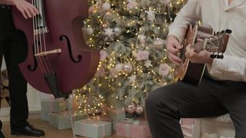 Zwei Männer spielen Weihnachtslied auf Akustikgitarre und Cello in der Nähe des dekorierten Neujahrsbaums in Girlandenlichtern. glückliche Familie feiert Heiligabend. foto