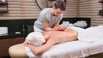 Masseur macht Massage des Rückens der Frau, die im Schönheitssalon liegt. professional massiert und berührt die Haut der Kundin mit traditionellen Techniken. foto