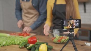 Junges Paar, das zusammen kocht und Video-Food-Blog vor der Kamera in der Küche zu Hause aufnimmt. Fokus auf Telefonbildschirm foto