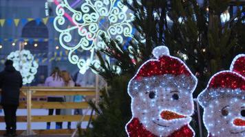 Weihnachtsspielzeug-Schneemänner auf dem Hintergrund der Eisbahn. foto