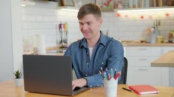 junger Mann freiberuflicher Student mit Laptop, der online von zu Hause aus im Internet arbeitet, lächelnder, fokussierter tausendjähriger Typ, der auf dem Computer tippt, der im Internet surft und auf den Bildschirm schaut foto